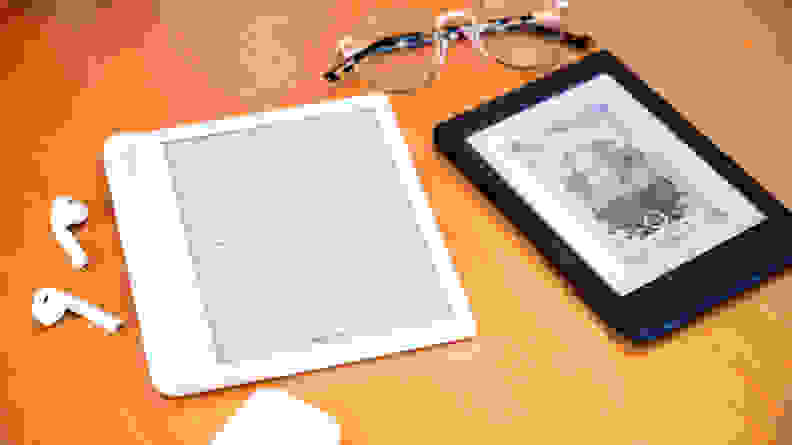 Two Kobo e-readers sitting on a desktop with a pair of glasses and a set of AirPods.