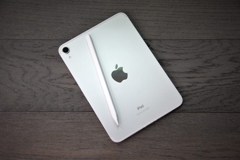 An Apple iPad Mini 6th-gen with Apple Pencil laid on top of it.