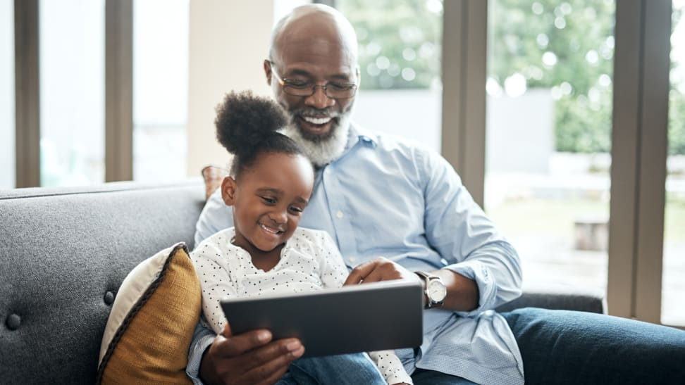 Grandfather and child sitting on a couch with a tablet