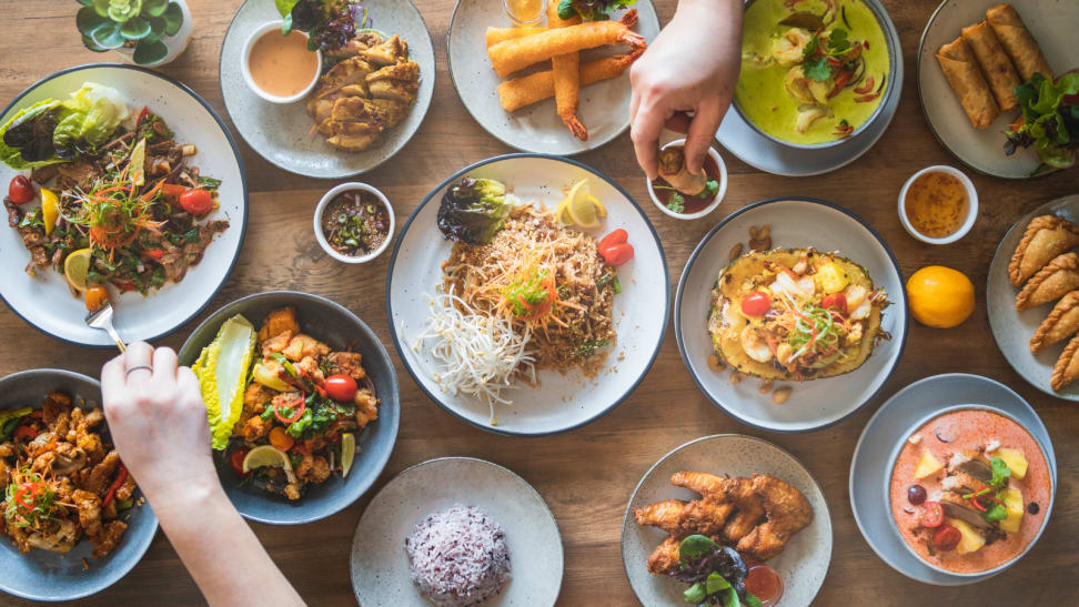 On a dinner table, dishes of various styles and cuisines are on display, including shrimp tempura(shrimp fried in batter), nasi goreng, and Thai green curry.