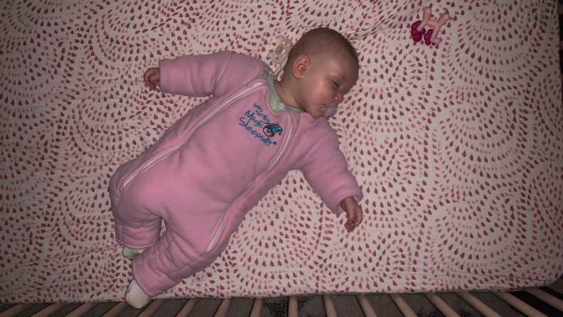 An infant lays in a crib wearing a pink sleepsuit.