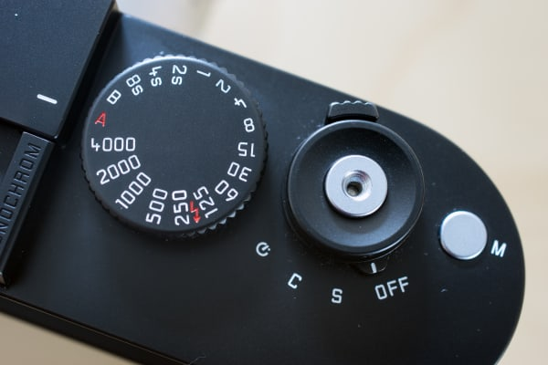 The top of the controls include a shutter speed dial, shutter release button, movie button, and power switch.
