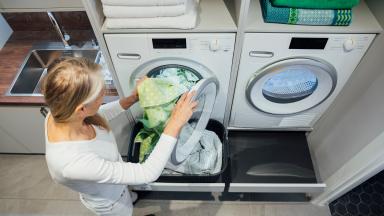 A person puts daily washing into the washing machine.