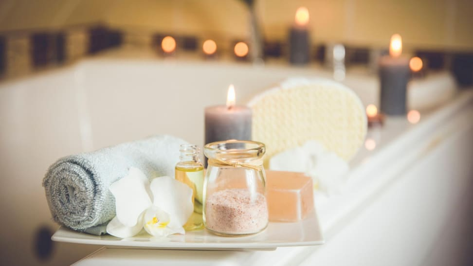 A bathtub with lit candles surrounding and a bath tray with a towel, bath salts, and a large candle