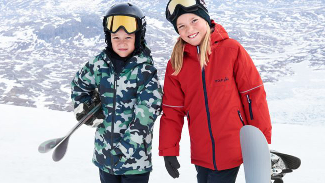 Two young kids in the snow wearing ski parkas and carrying skis