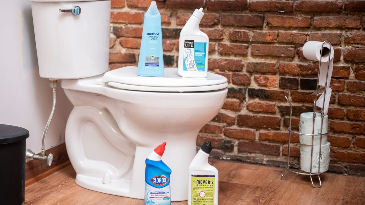 Four bottles of toilet bowl cleaner stand on top of and next to a toilet