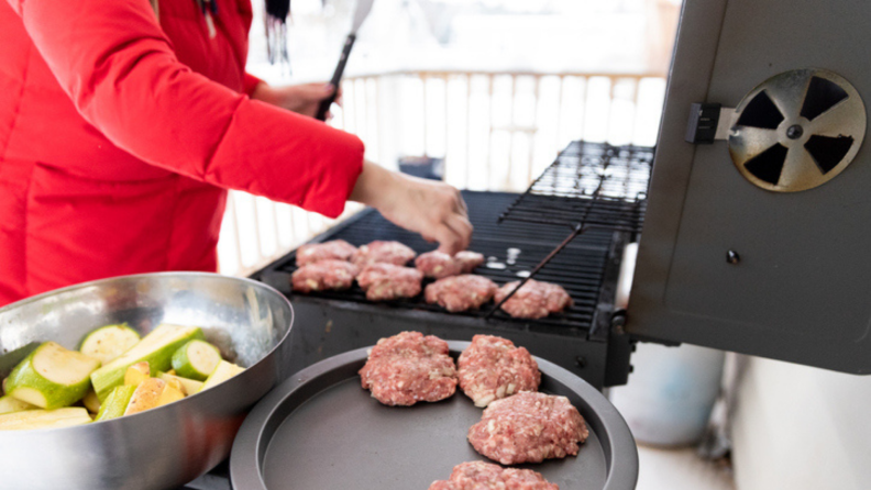 Person in red puffy coat cooking burger patties and vegetables on grill during winter
