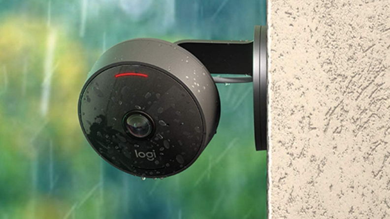 A weatherproof outdoor security camera from Logitech is pictured hanging on the side of a home.