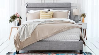 The Allswell supreme mattress with a gray bed frame and tan blankets