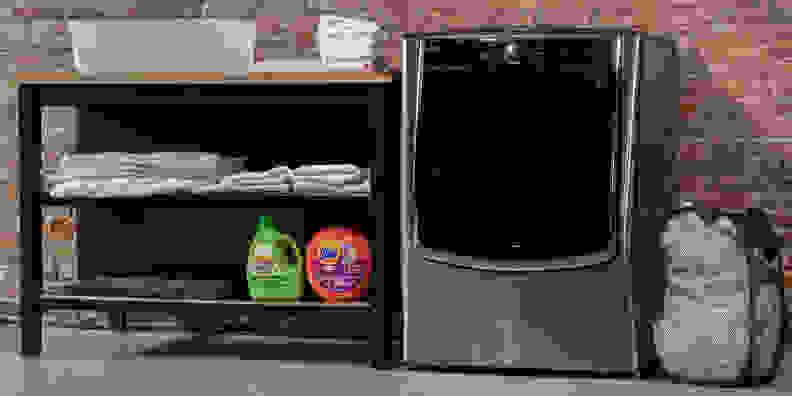 The LG WM9000HVA in a laundry room beside a set of shelves.