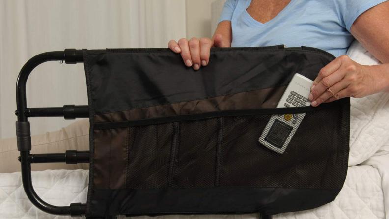 A person tucks a remote control into a net.