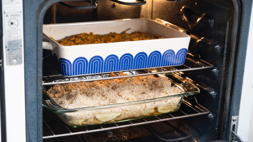 Inside an oven, the Great Jones Hot Dish sits on the top rack, and a Pyrex dish is on the bottom rack.
