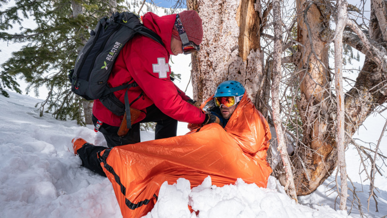 A paramedic helps a person into an emergency divvy on a snowy hill.