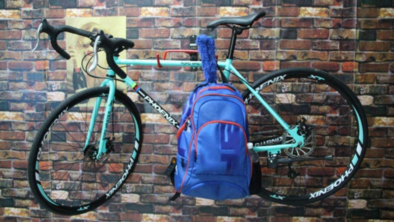 Bike on a bike wall mount with a backpack attached on a brick backdrop
