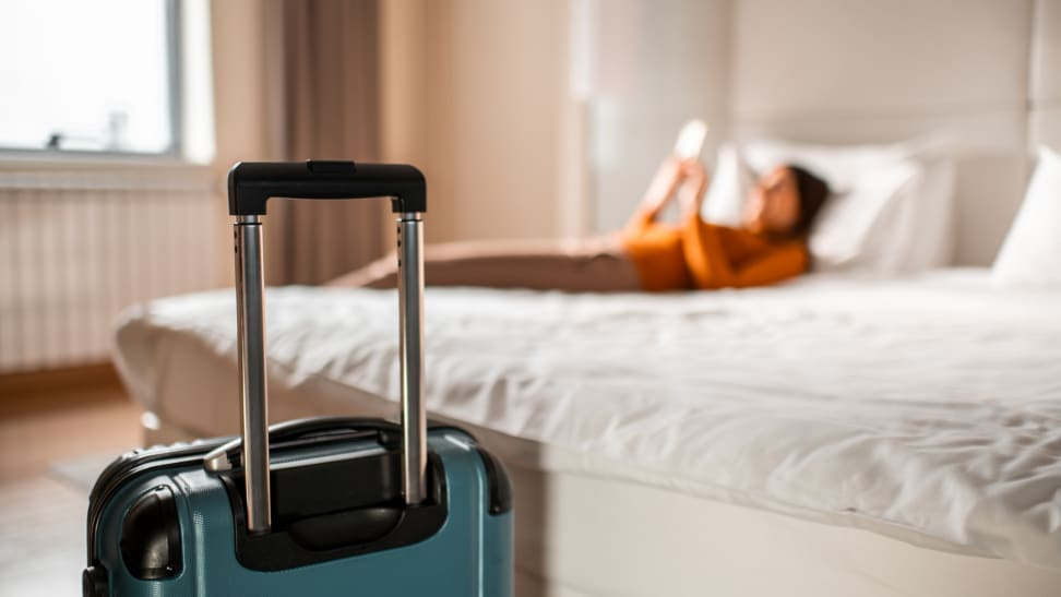 A person is laying on their hotel room bed looking at their phone. A suitcase is at the foot of the bed.