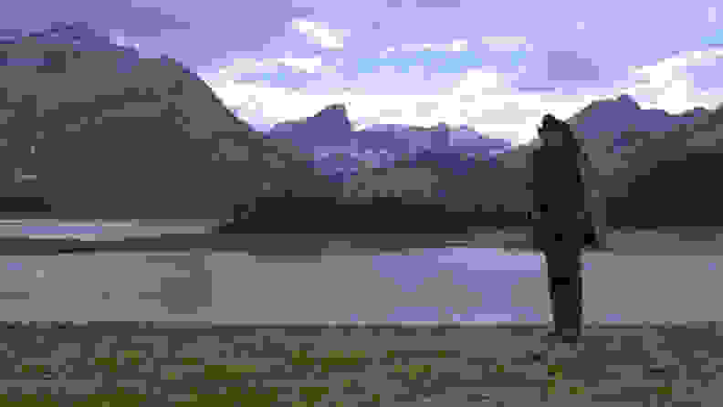Jack (Jake Gyllenhaal) stands alone beside a river with the mountains in the background.
