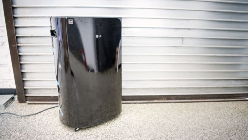 A black dehumidifier sitting on the ground with a filter behind it