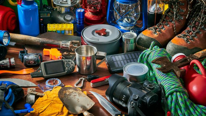 An assortment of camping equipment on a floor.