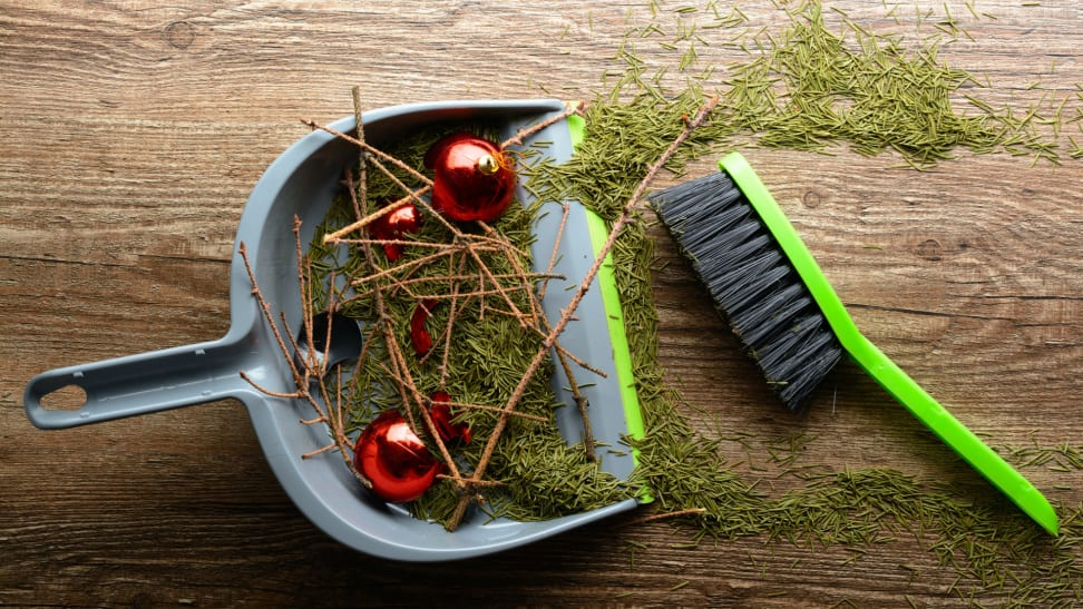 Pine needles, twigs, and red ornaments in a sweeping dustpan next to a handheld broom