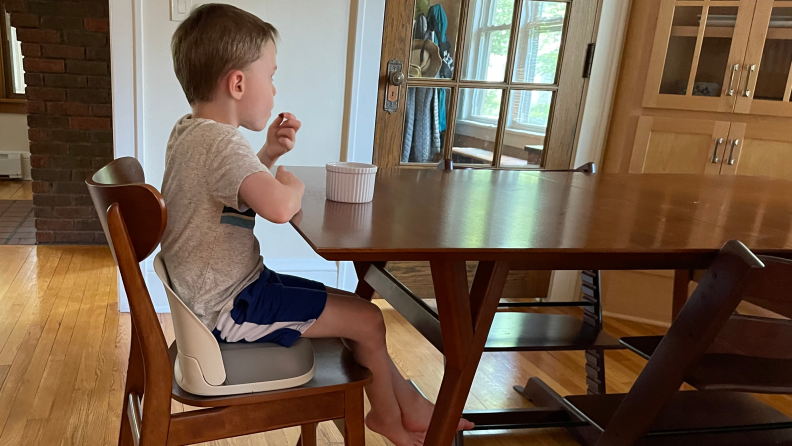 A boy sitting on a booster seat at a dining room table eating from a small white bowl.