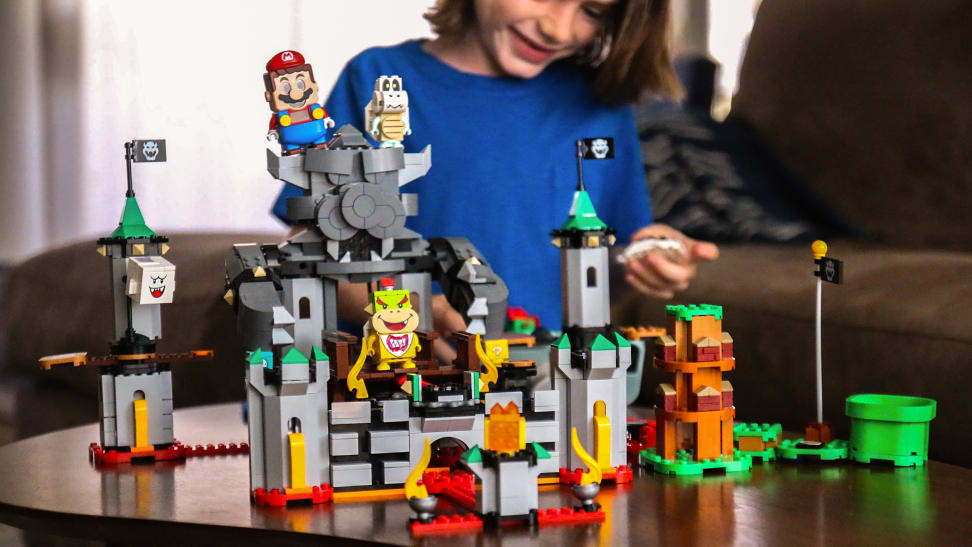 A boy smiles in the background as he assembles the Super Mario Bowser's Castle Lego set.