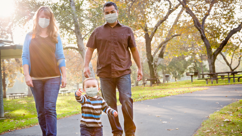 Family on a walk wearing masks.