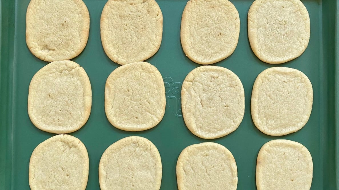 Sugar cookies on a green cookie sheet.