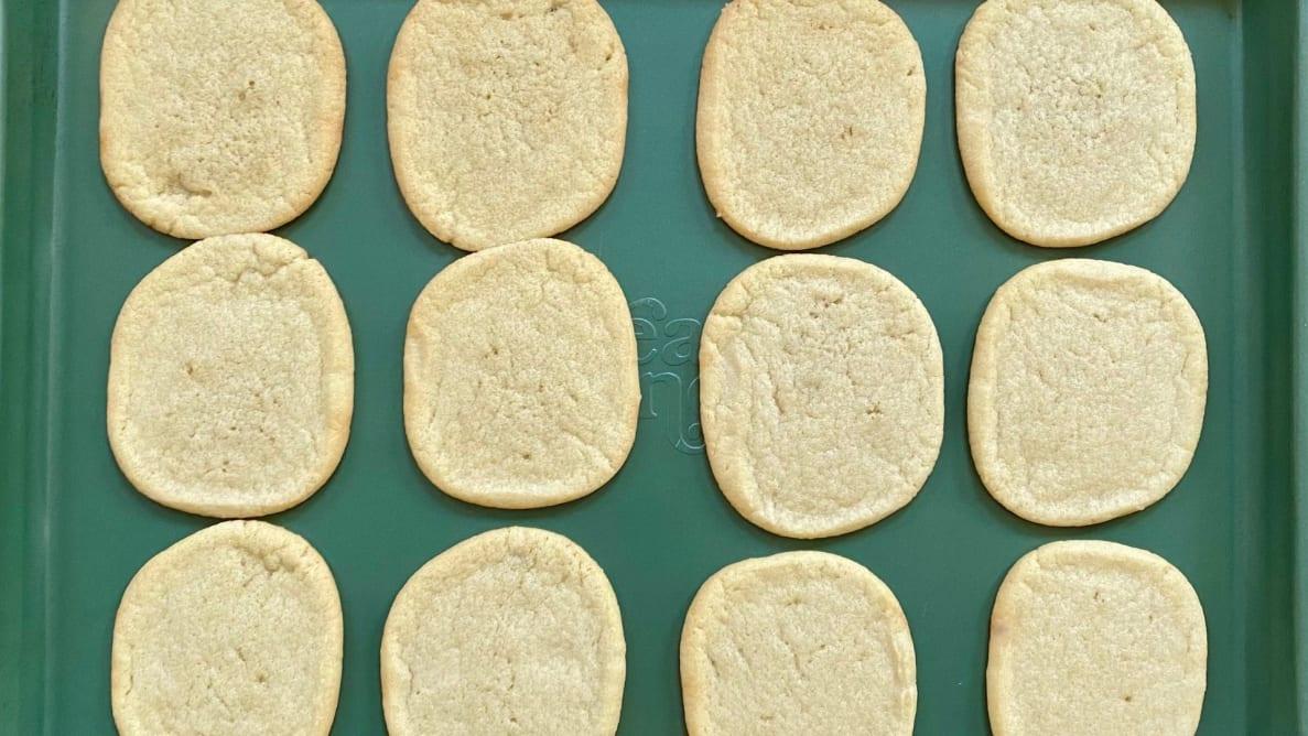 Sugar cookies on a green cookie sheet.