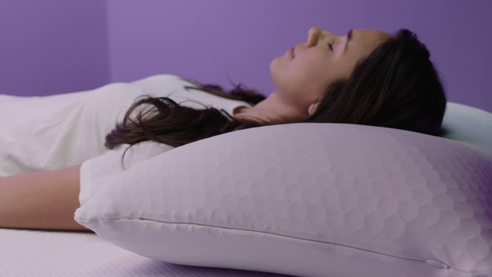 A woman sleeps on the purple harmony pillow on her back