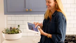 A woman standing in a kitchen holding a digital calendar