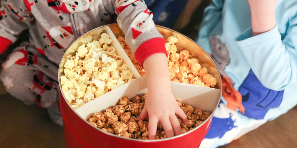 Kids in pajamas enjoy popcorn from a tin