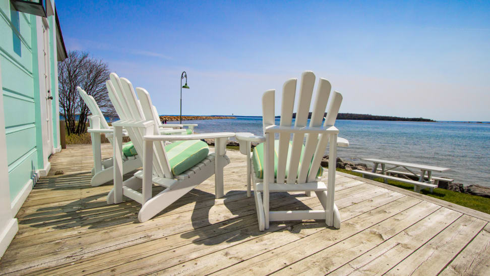Three Adirondack chairs outside facing the ocean.