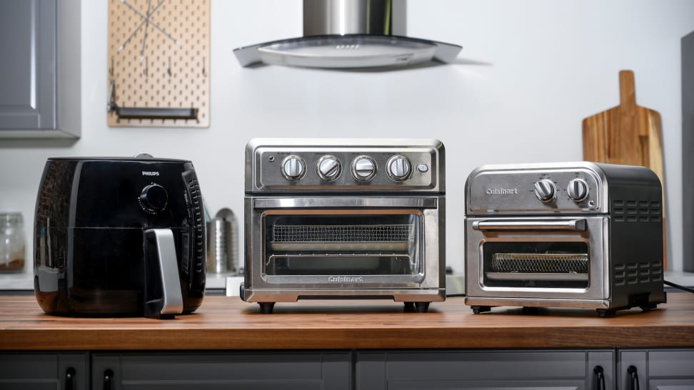 Philips and Cuisinart air fryers are lined up on a kitchen counter.