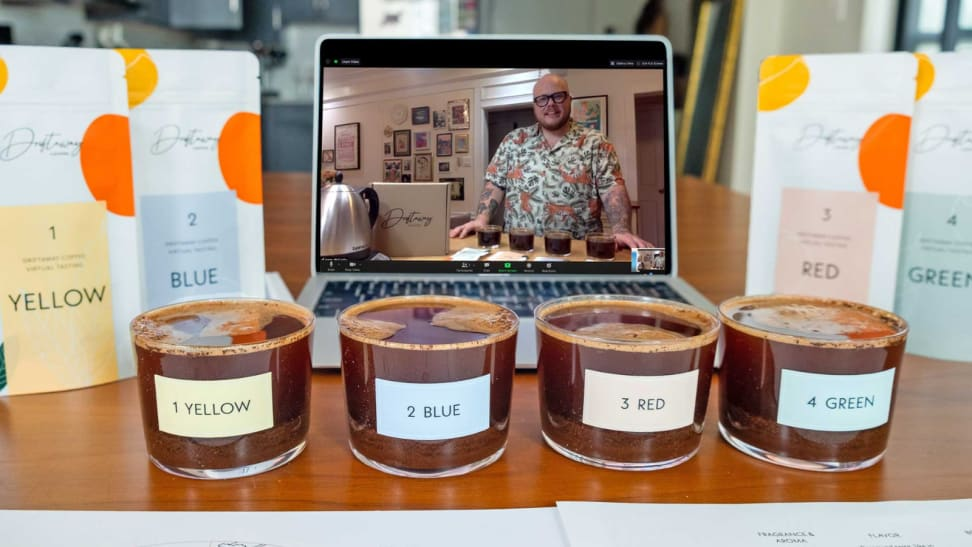 A virtual coffee tasting setup including a laptop streaming the class, clear cupping glasses with colored labels filled with the different coffees, and the corresponding colored coffee bean bags from Driftaway.