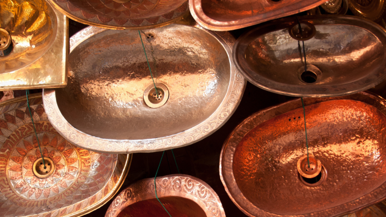 Handmade brass and copper sinks sit on display at a market.