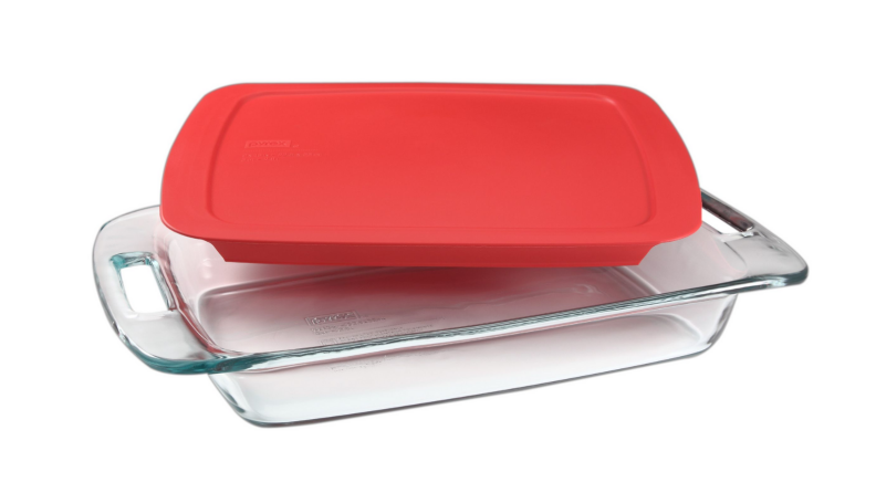 An image of a glass Pyrex baking dish with a red lid sat slightly askew on top of it, on a white background.