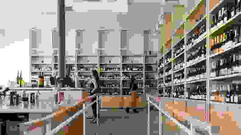 Four people shop for wine in a brightly lit natural wine store with light wood shelves filled with colorful bottles.