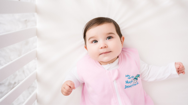 A baby wearing a pink onesie lays in a crib.