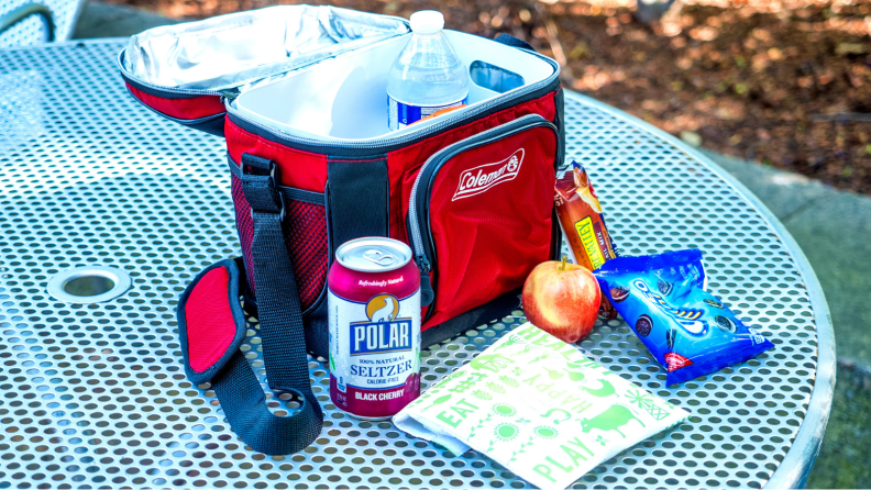 On an outdoor picnic table, there's a half-opened Coleman lunch cooler, with a can of soda, a lunchskins sandwich bag, an apple, and Oreos next to it.