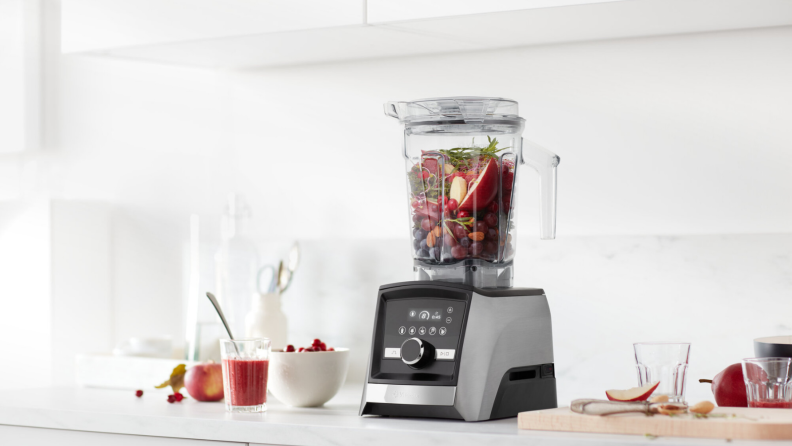 On a counter, there's a Vitamix Ascent Series A3500 blender with grey stainless steel finish. The blending cup is packed with apples and green vegetables, ready to make smoothies.