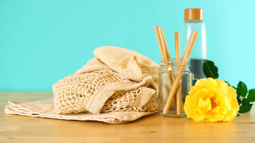 A reusable bag, straws, and glass container and yellow flower against teal background.
