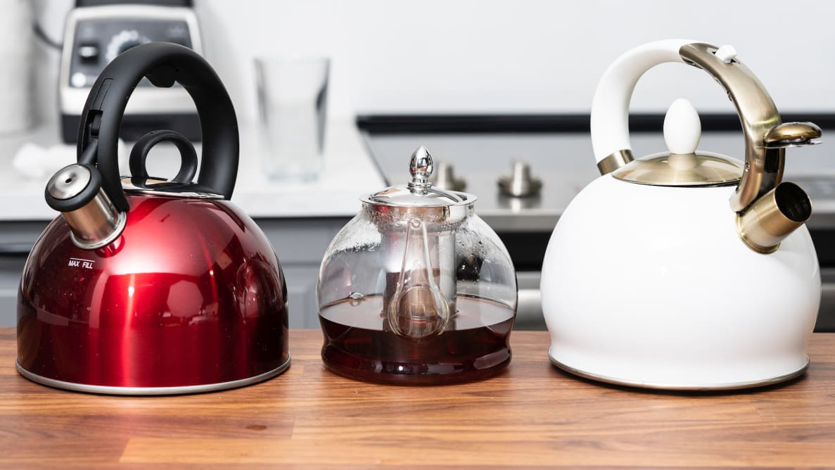 Three tea kettles, including the Cuisinart Aura, the Hiware glass kettle and the Susteas teapot, sit on a kitchen counter.