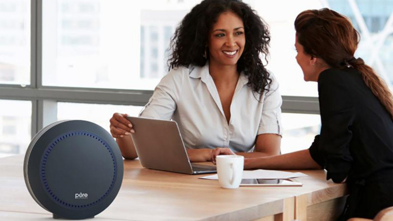 An air purifier sits on a table while two people work.