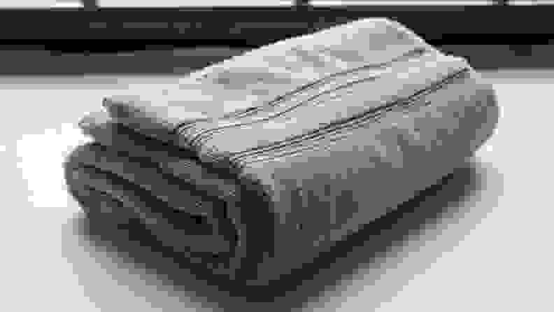 A towel folded up and on a table.