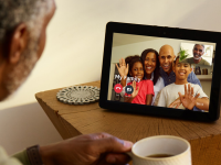 A man chats with a group of people using an Amazon Echo Show (second-generation)