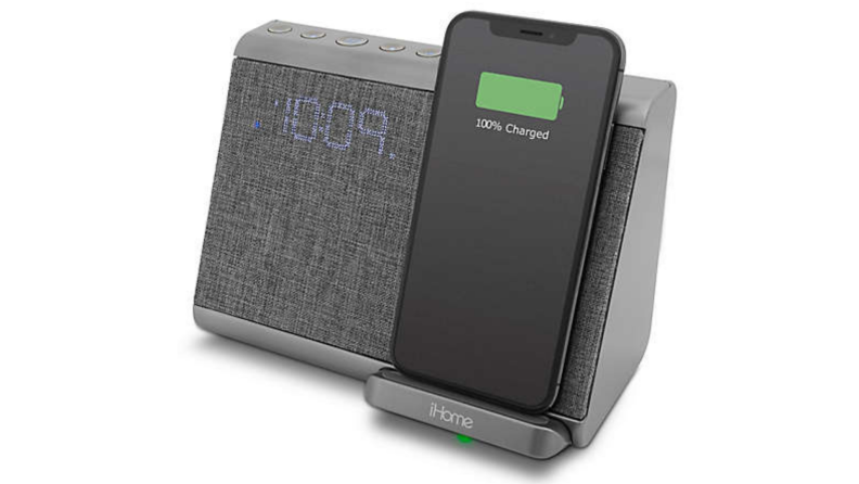 A grey alarm clock against a white background. Includes an iPhone charging station. iPhone is pictured.