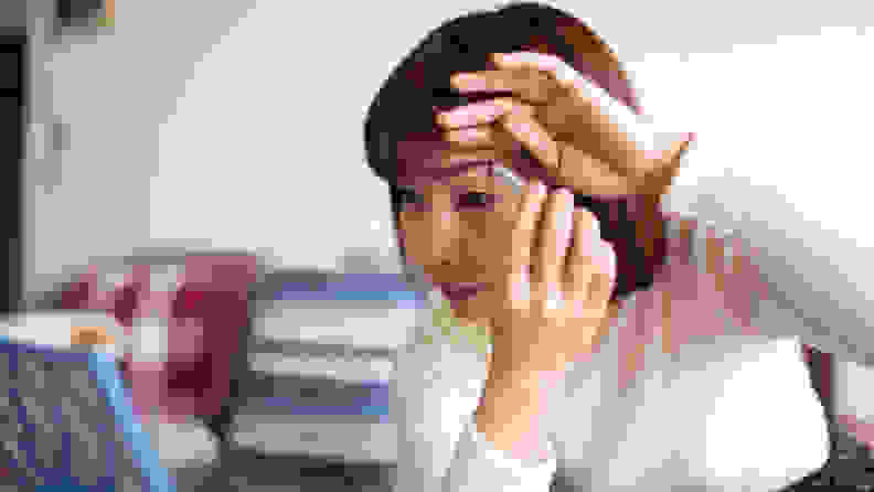 An older, Asian person holds an eyebrow pencil with her right hand and pulls her face taut to apply the pencil to her left eyebrow.