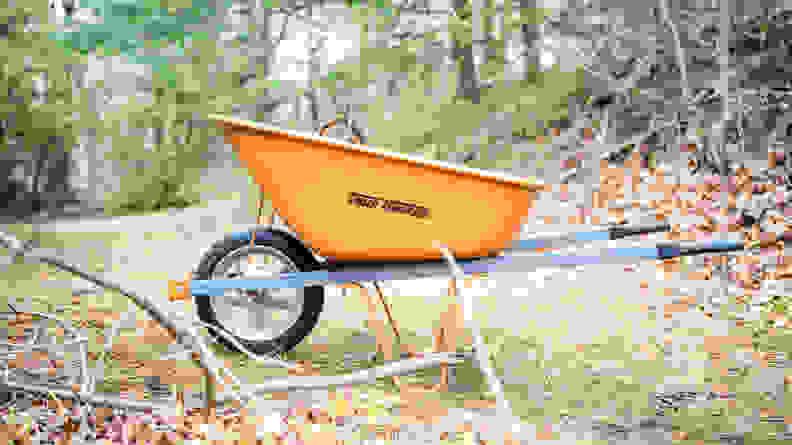 An orange True Temper wheelbarrow sits in a wooded area.