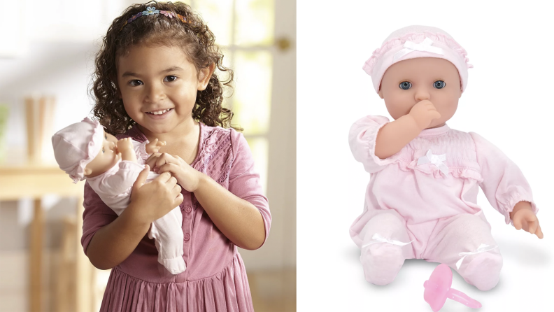 A little girl holds a baby doll