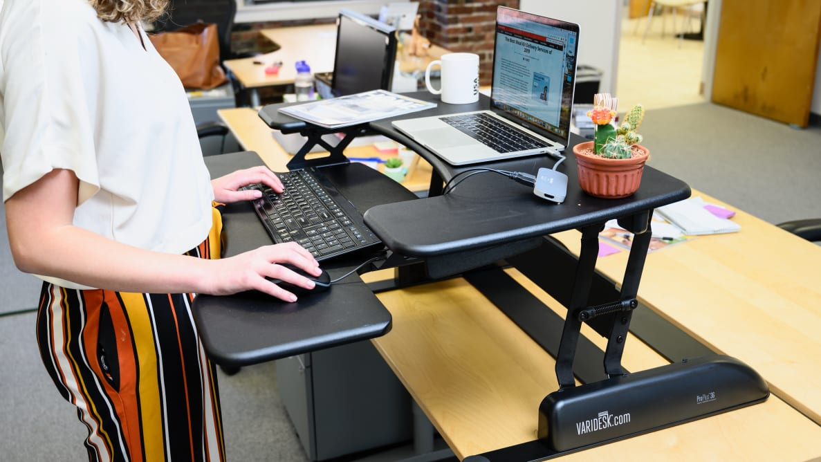 Photo of a Reviewed journalist working at a standing desk.